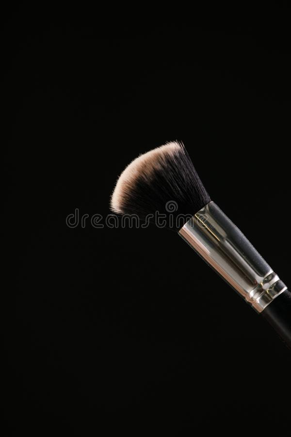 Componga los cepillos cosméticos con el polvo para ruborizarse explosión en fondo negro fotos de archivo libres de regalías