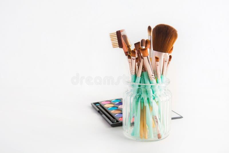 Componga los cepillos de los cosméticos en el tarro de cristal con la sombra de ojos en el fondo blanco con el espacio de la copi imagen de archivo