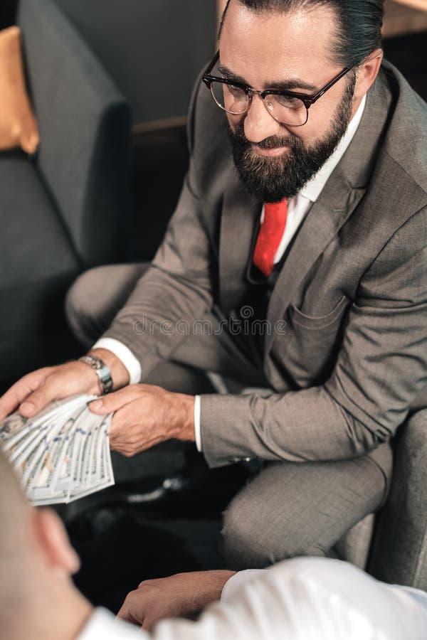 Comportamiento barbudo del abogado ilegal mientras que recibe el soborno de cliente fotografía de archivo libre de regalías