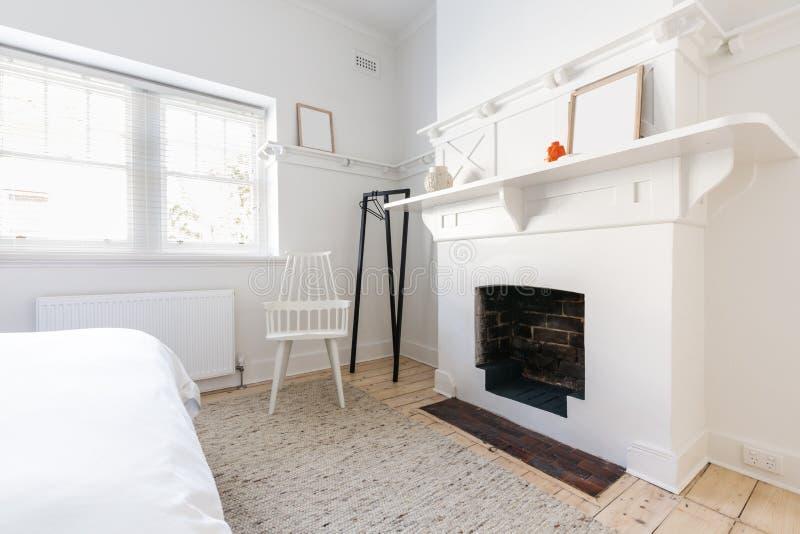 Comportez la cheminée dans une chambre à coucher dénommée danoise rénovée par luxe photo stock
