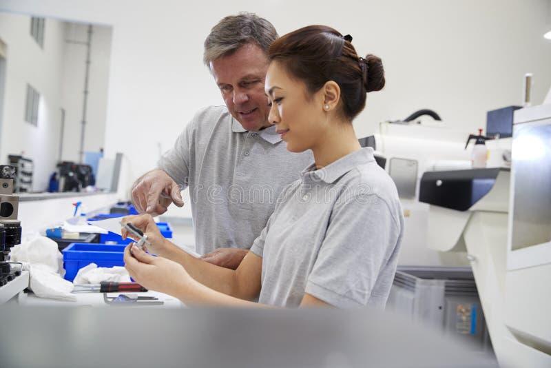 Composants de mesure d'And Female Apprentice d'ingénieur dans l'usine photos stock