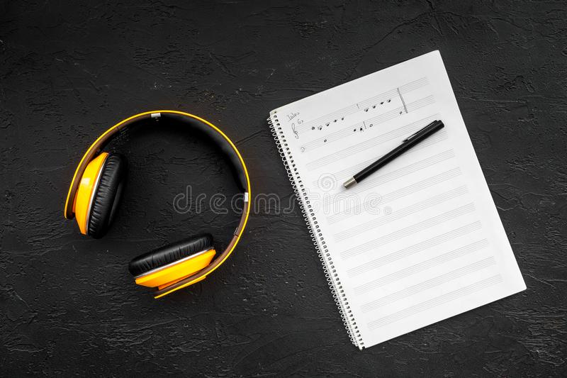Composer and song writer desktop with headphones and notes on black background top view mock up stock photos