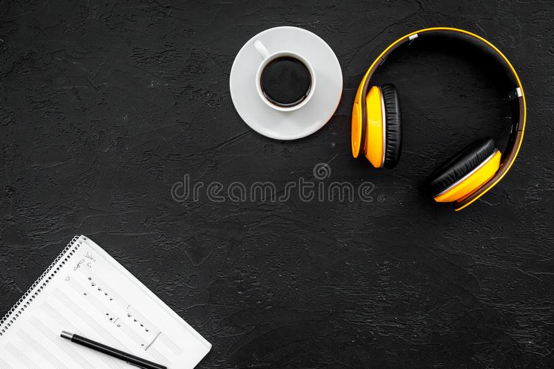 Composer and song writer desktop with headphones and notes on black background top view mock up stock photo