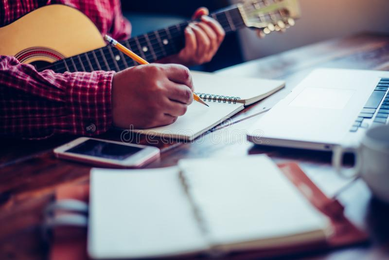 Composers are writing songs on the table with guitars.  royalty free stock images