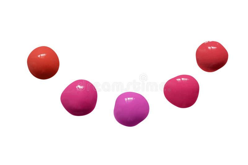 Composez l'échantillon Placez des baisses de lustre de lèvre dans différentes couleurs lumineuses d'isolement sur le fond blanc T photographie stock