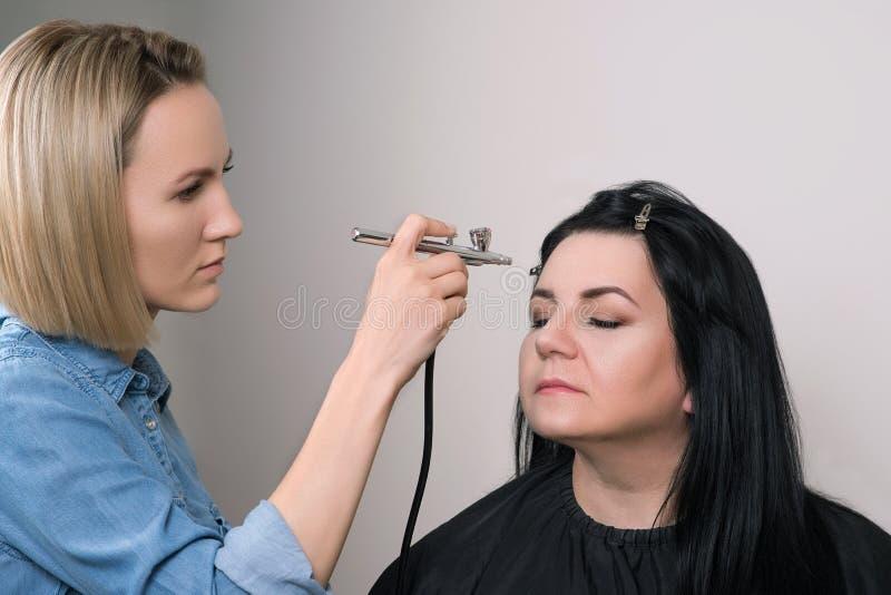 Composez l'artiste faisant le maquillage professionnel de la femme mûre Composez dans le processus Maquillage d'aerographe photographie stock