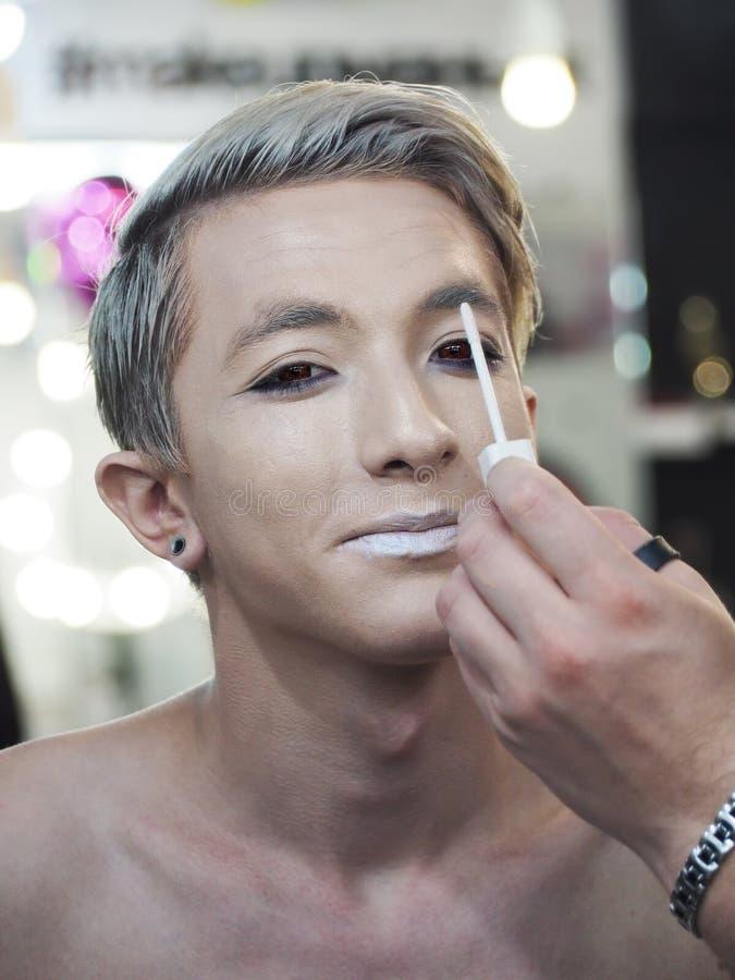 Composez l'artiste fait le maquillage au modèle en gros plan de yeux souriant et regardant la caméra image stock