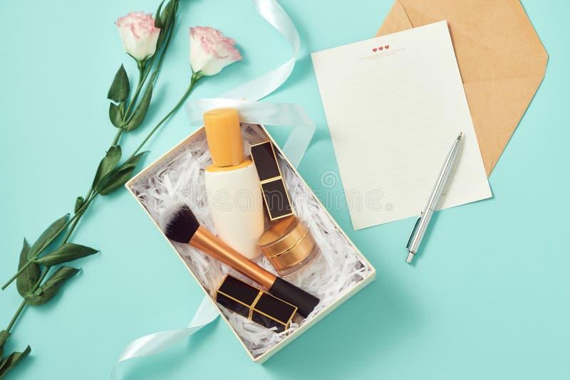 Composez le boîte-cadeau avec le sérum, rougissez, les brosses, la crème et les rouges à lèvres à l'intérieur image stock