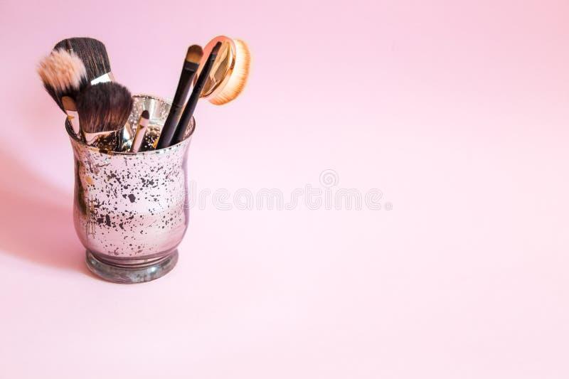 Composez les brosses dans un verre sur le fond rose L'espace pour le texte photographie stock