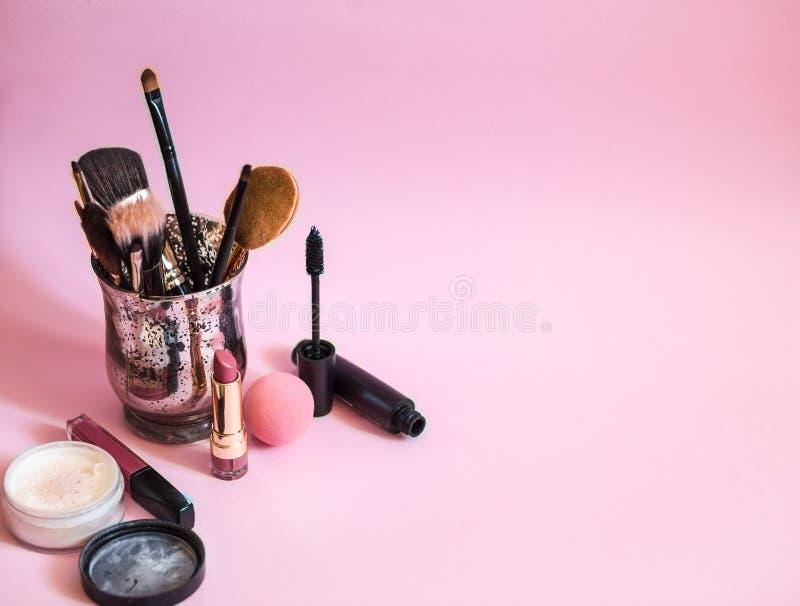 Composez les brosses dans un verre sur le fond rose L'espace pour le texte photo stock