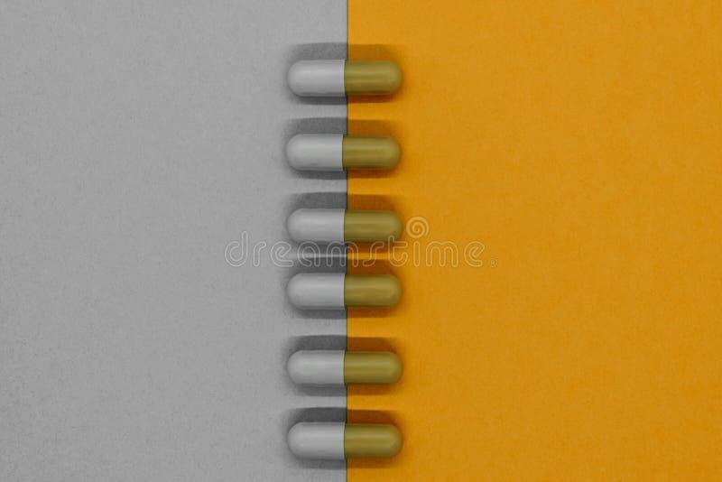 A composição abstrata do separado em cinzento e na laranja colore comprimidos da medicamentação e coloca na linha vertical fotografia de stock royalty free