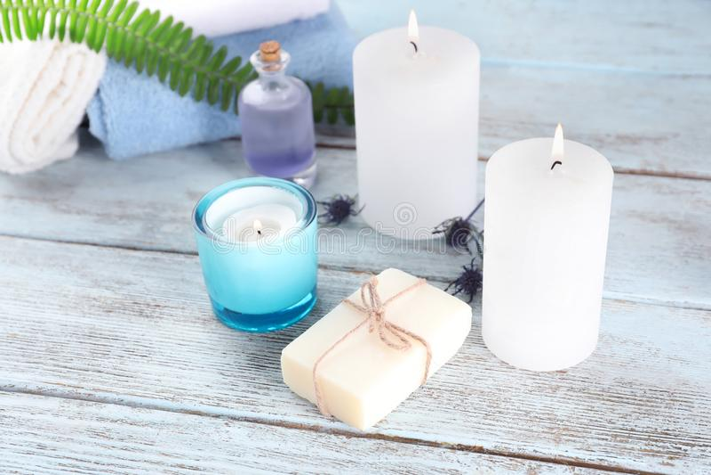 Composição bonita dos termas com sabão natural e velas ardentes no fundo de madeira imagem de stock royalty free