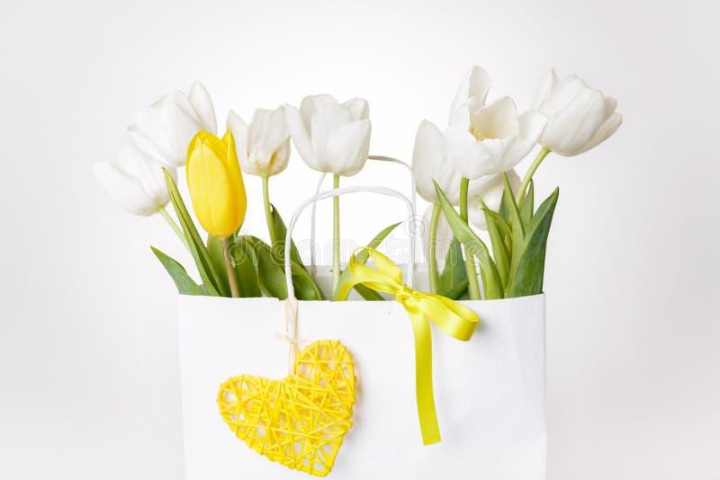 Composição branca, amarela festiva das tulipas, coração feito a mão, fita no fundo branco Ramalhete de flores da mola no saco de  fotografia de stock