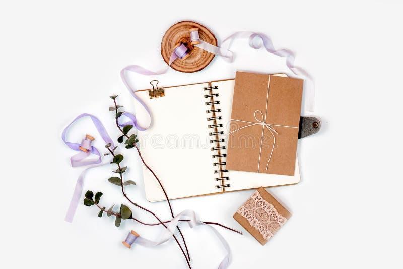 Composição brilhante com um caderno espiral, um eucalipto, umas fitas de seda e um papel de embalagem em um fundo branco Fotos pa fotografia de stock royalty free