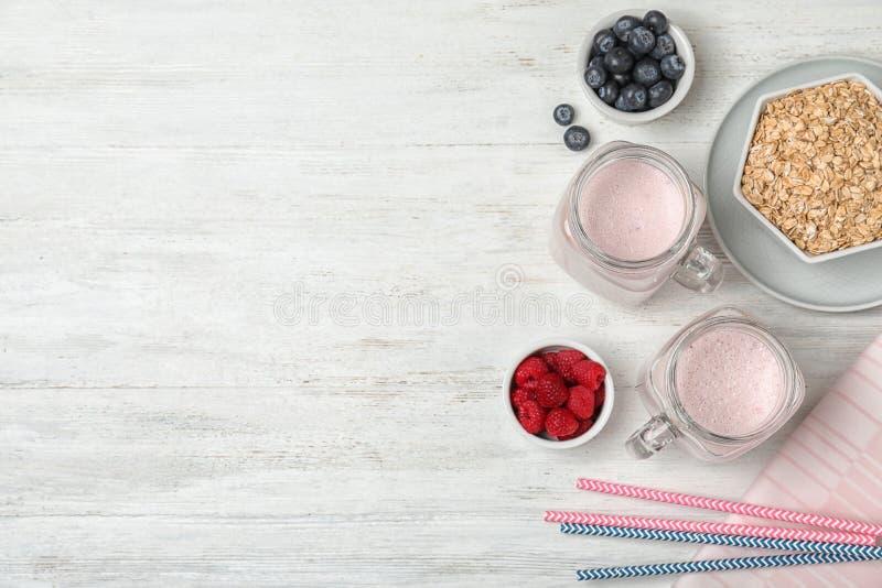 Composição colocada lisa com agitação saudável da proteína em uns frascos, em uns ingredientes e em um espaço de pedreiro para o  imagem de stock royalty free