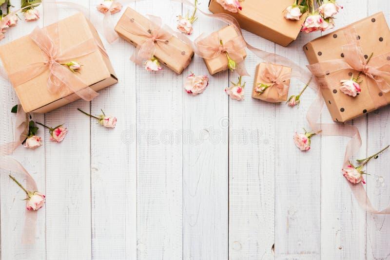 Composição colocada lisa com as caixas de presente envolvidas no papel de embalagem e na rosa imagem de stock royalty free