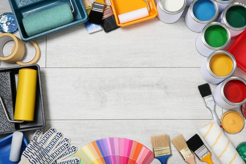 Composição colocada lisa com as latas de ferramentas da pintura e do decorador no fundo de madeira imagens de stock royalty free