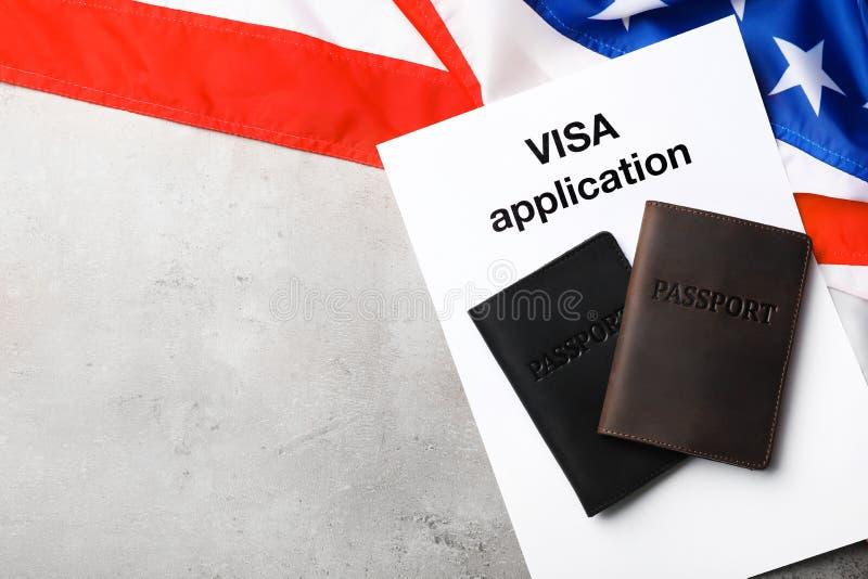 Composição colocada lisa com a bandeira dos EUA, dos passaportes e da aplicação de visto no fundo cinzento fotos de stock royalty free