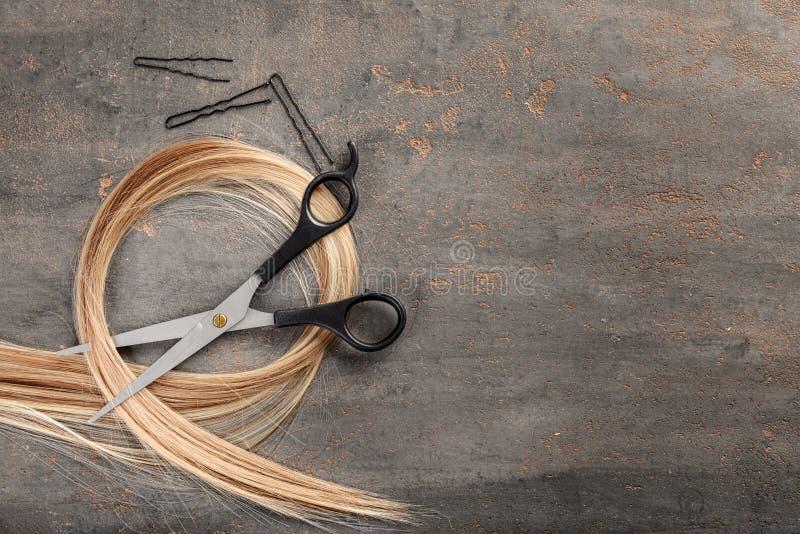 Composição colocada lisa com cabeleireiro \ 'ferramentas de s e costa do cabelo louro no fundo cinzento fotografia de stock