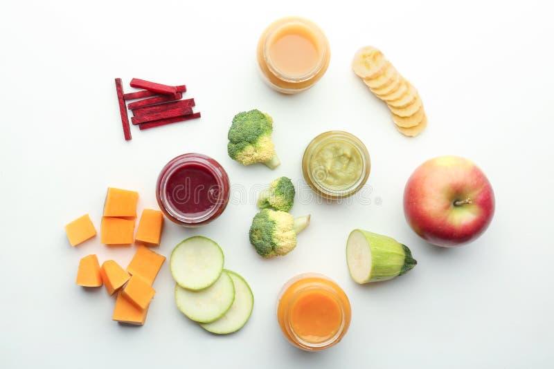 Composição colocada lisa com comida para bebê e os ingredientes saudáveis no fundo branco imagens de stock