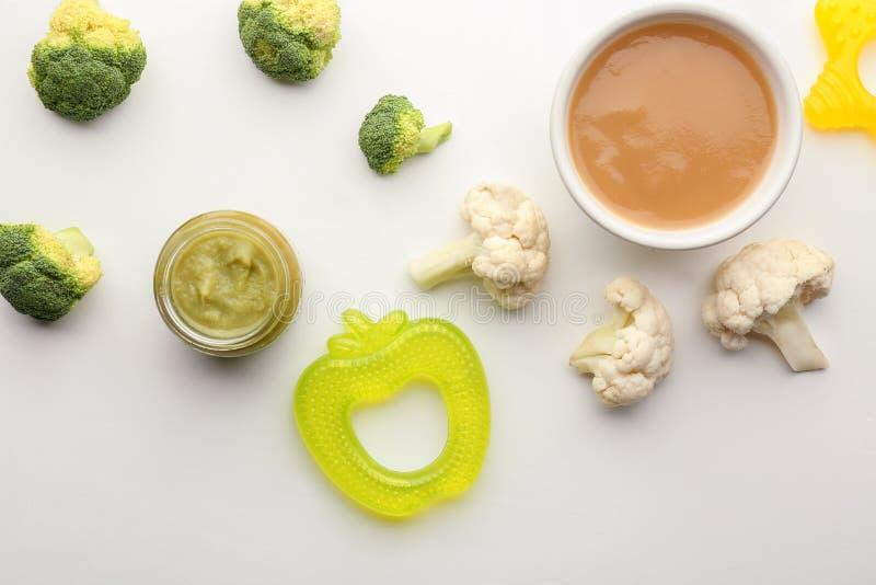 Composição colocada lisa com comida para bebê e os ingredientes saudáveis no fundo branco fotos de stock royalty free