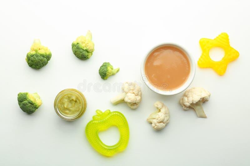 Composição colocada lisa com comida para bebê e os ingredientes saudáveis no fundo branco foto de stock royalty free