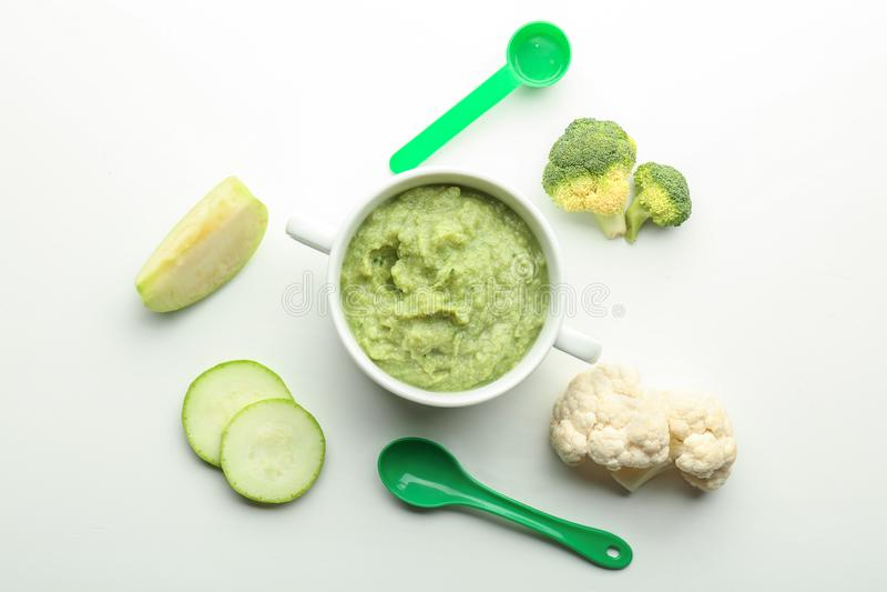 Composição colocada lisa com comida para bebê saudável na caçarola e ingredientes no fundo branco imagem de stock royalty free