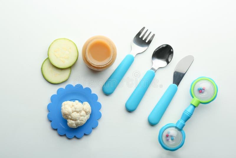 Composição colocada lisa com comida para bebê saudável no frasco, na cutelaria e nos ingredientes de vidro no fundo branco fotografia de stock royalty free