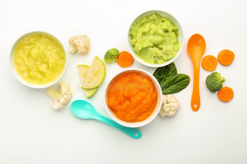 Composição colocada lisa com comida para bebê saudável no fundo branco fotografia de stock royalty free