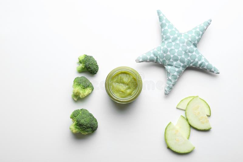 Composição colocada lisa com comida para bebê saudável no fundo branco fotos de stock