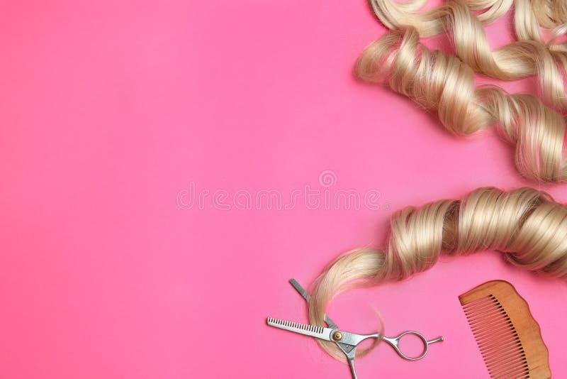 Composição colocada lisa com fechamentos e ferramentas do cabelo no fundo da cor imagem de stock