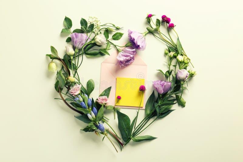 Composição colocada lisa com flores e envelope no fundo claro imagens de stock royalty free