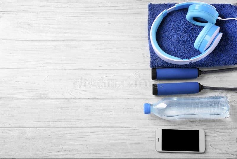 Composição colocada lisa com a garrafa da água, da corda de salto, dos fones de ouvido e do smartphone no fundo de madeira Exerc? fotografia de stock