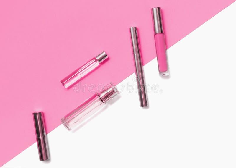 Composição colocada lisa com os produtos de composição decorativos e parfume no fundo branco cor-de-rosa e isolado vívido Composi imagens de stock