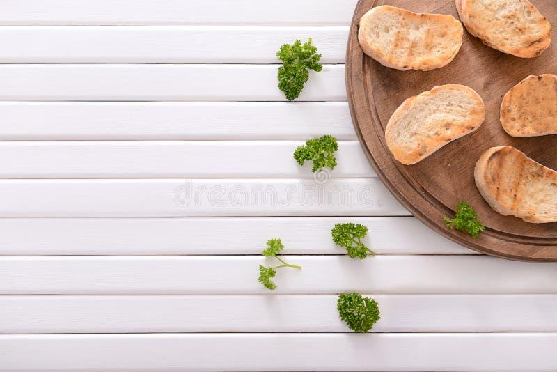 Composição colocada lisa com pão brindado saboroso e salsa no fundo de madeira fotos de stock royalty free