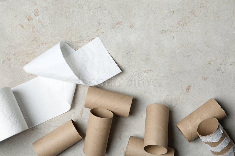 Composição colocada lisa com papel higiênico e rolos vazios no fundo cinzento imagens de stock
