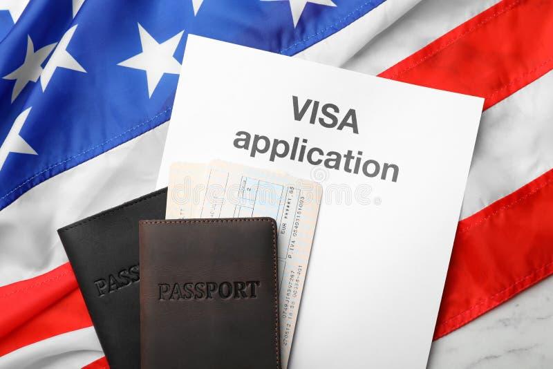 Composição colocada lisa com passaportes e aplicação de visto na bandeira foto de stock