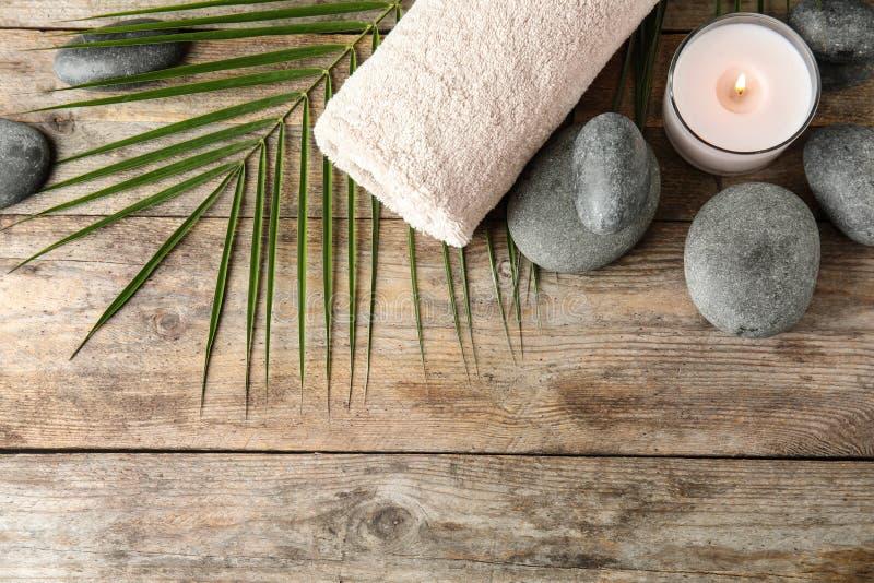 Composição colocada lisa com pedras, toalha e vela do zen no fundo de madeira imagens de stock