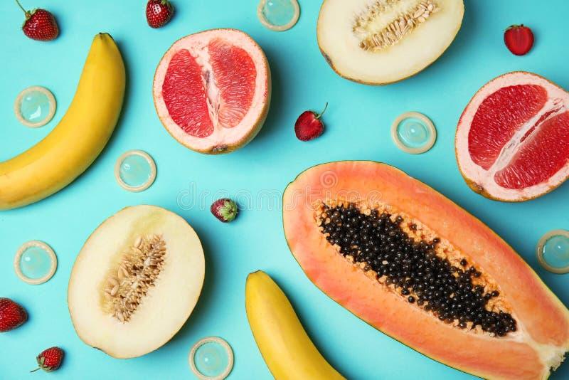 Composição colocada lisa com preservativos e frutos exóticos no fundo de turquesa erotic fotografia de stock