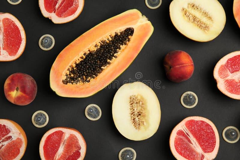 Composição colocada lisa com preservativos e frutos exóticos no fundo preto erotic fotografia de stock royalty free