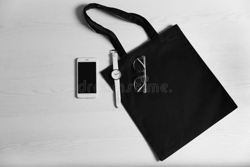 Composição colocada lisa com sacola, smartphone e acessórios do eco no fundo de madeira branco imagem de stock