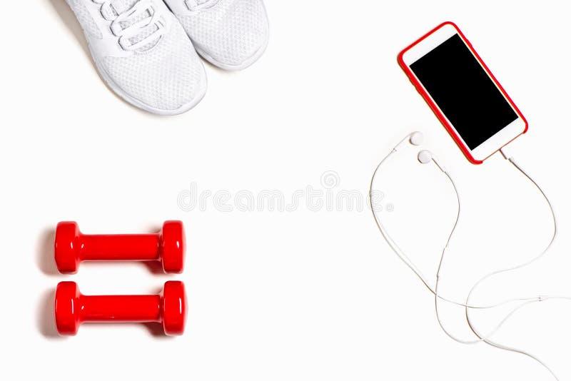 Composição colocada lisa com sapatilhas, fones de ouvido, telefone celular e pesos vermelhos no fundo branco imagens de stock
