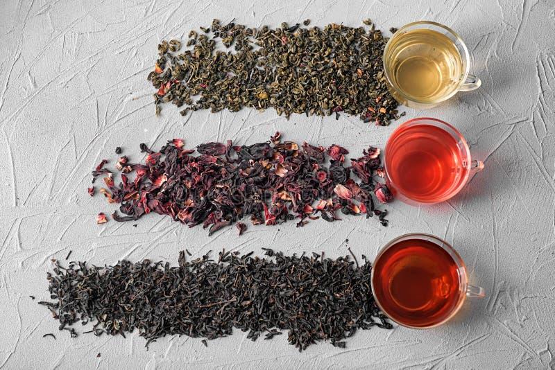 Composição colocada lisa com tipos diferentes de chá e de copos secos no fundo cinzento fotografia de stock