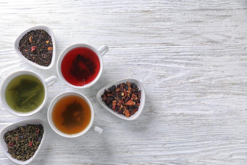 Composição colocada lisa com tipos diferentes do chá no fundo de madeira fotografia de stock royalty free
