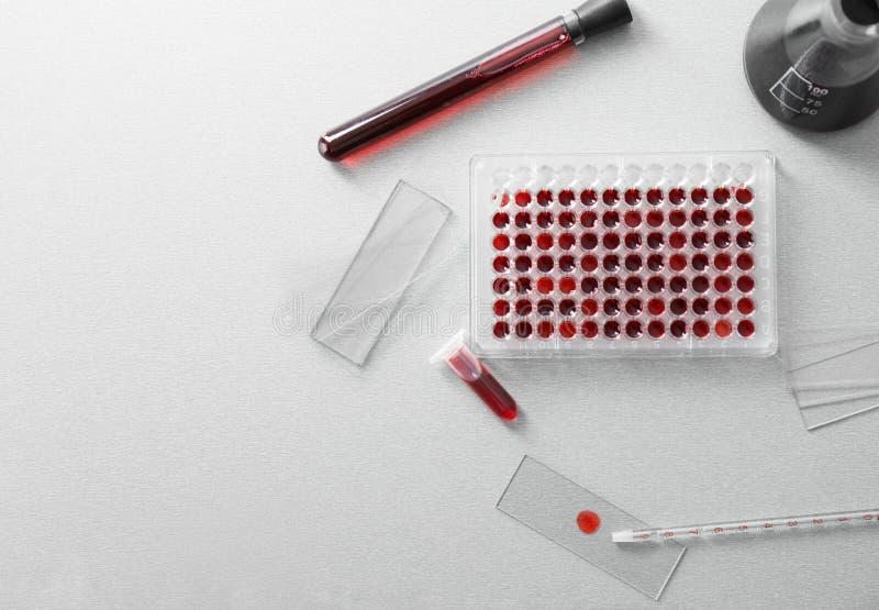 Composição colocada lisa com tubos de ensaio e amostras de sangue no fundo claro fotografia de stock