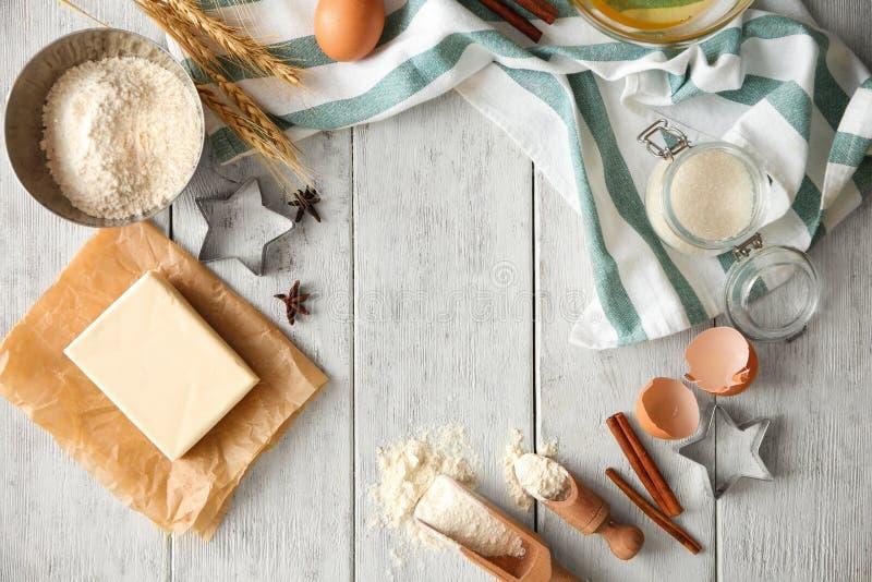Composição colocada lisa com utensílios e produtos da cozinha no fundo de madeira Oficina da padaria imagem de stock