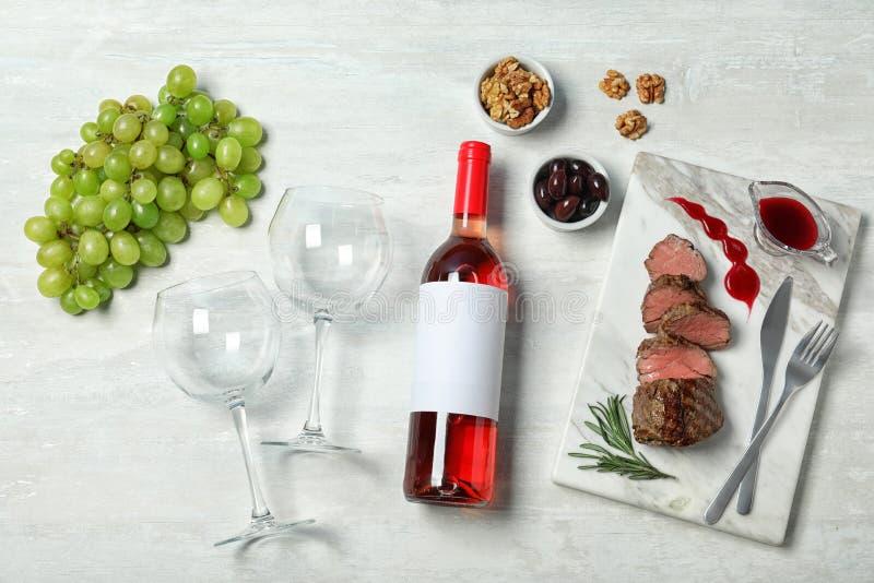 Composição colocada lisa com vinho e alimento no fundo branco imagens de stock
