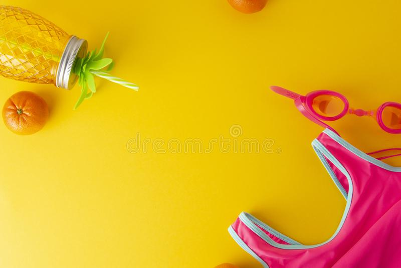 Composição colocada lisa, fundo colorido do verão com roupa de banho cor-de-rosa e objetos da praia no fundo amarelo Copie o espa imagens de stock