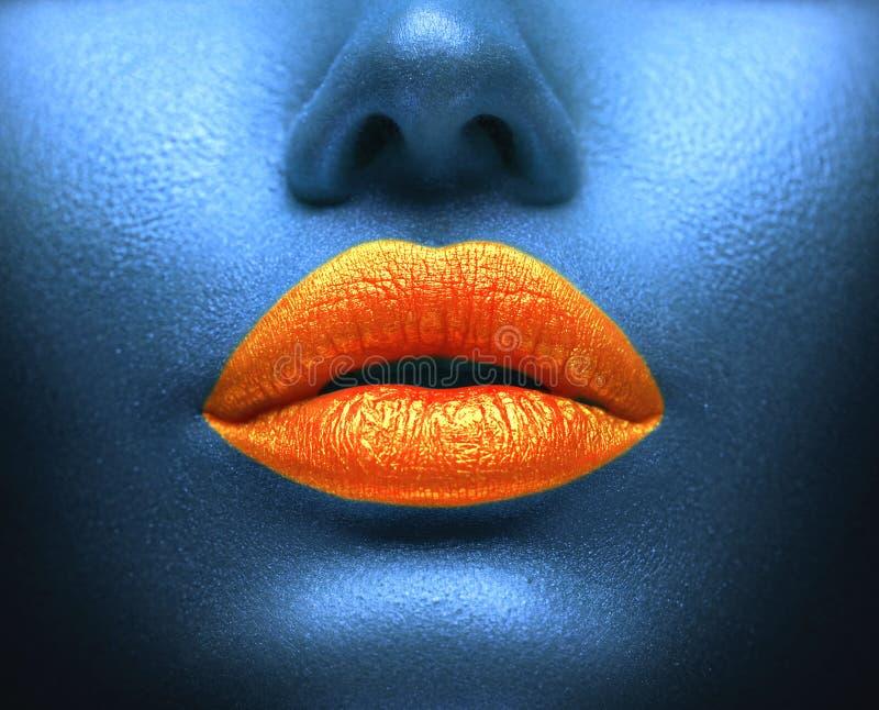Composição colorida criativa Bodyart, lipgloss nos bordos 'sexy', boca das meninas Bordos alaranjados na pele azul imagem de stock