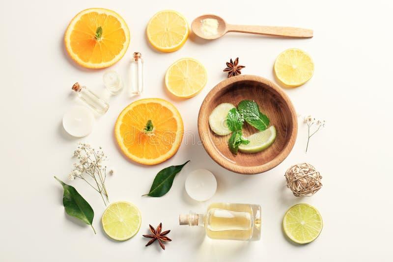 Composição com óleos essenciais e frutos cortados no fundo branco, vista superior foto de stock royalty free